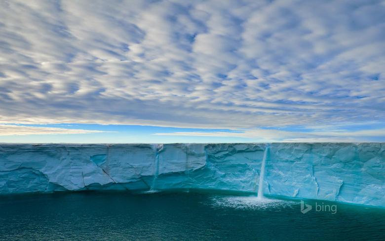 Meltwater creates waterfalls on an ice cap Svalbard Archipelago