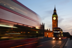 a long exposure shot of double decker buses near the houses of