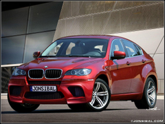 BMW X6M in metallic Ruby Red with black leather interior hmmm yes