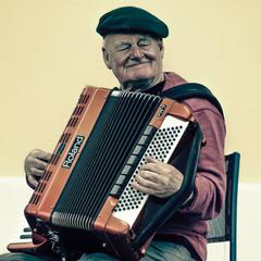 Man Sitting Playing Accordion Stock Photo