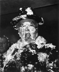A man s face is covered in cream as a result of a pie fight in the