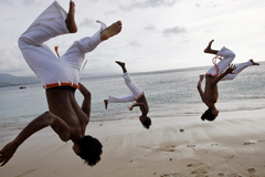 A group of men practice capoeira on the beach in Dili wallpapers