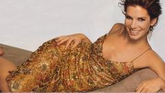 Sandra Bullock Smiling Laying Pose In Golden Dress Wallpapers
